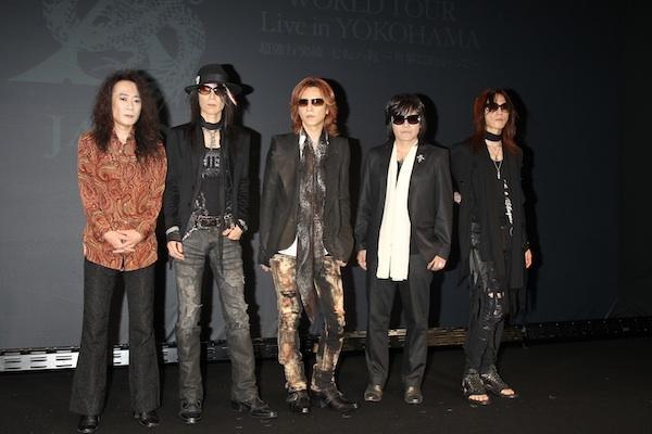 画面の前に立って並んでいるメンバー5人のX JAPANの画像